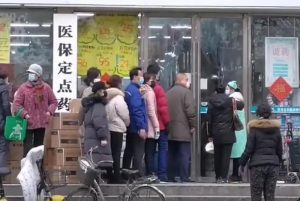citizens of wuhan lining up outside of a drug store to buy masks during the wuhan coronavirus outbreak