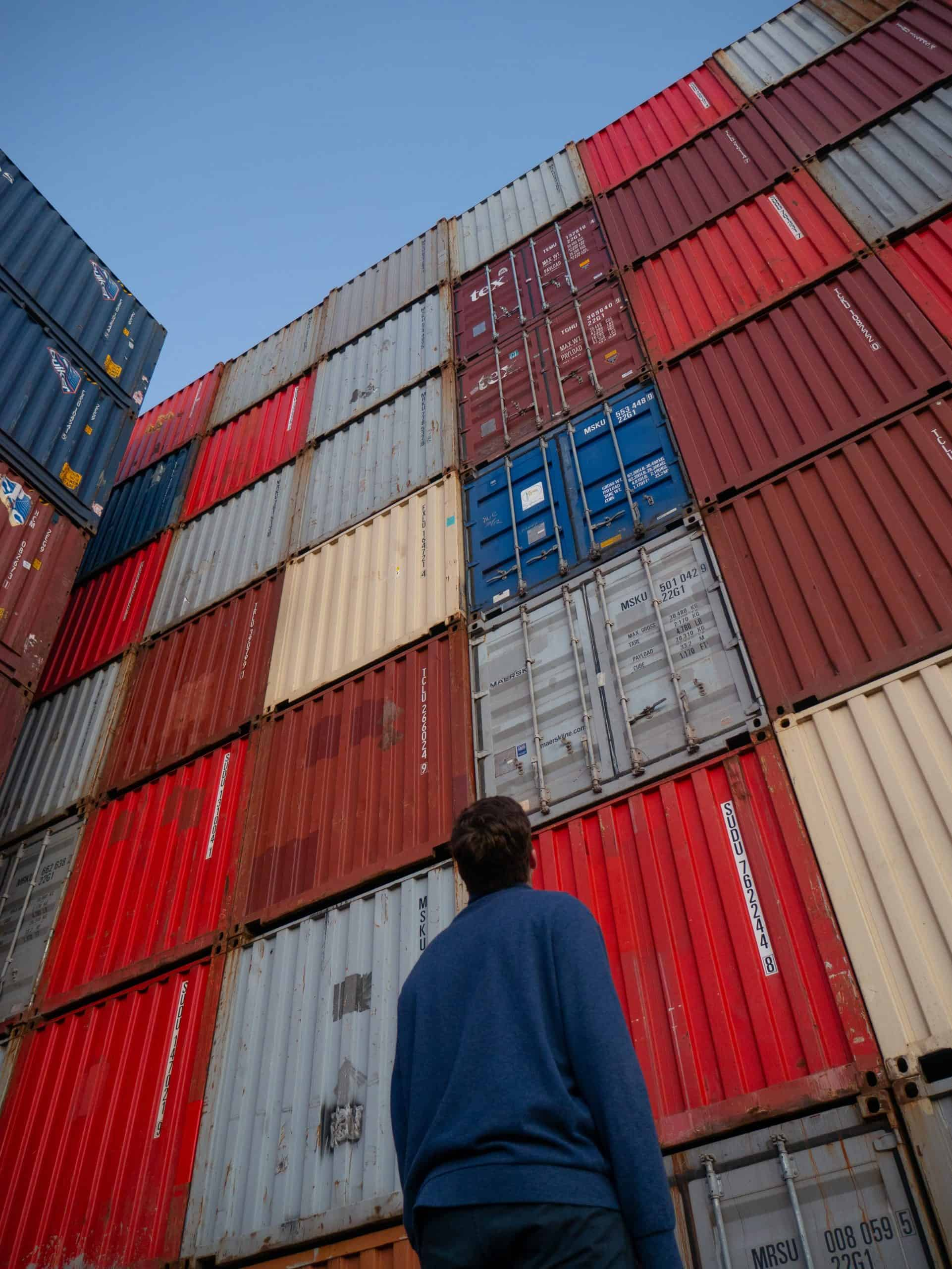 Man Looking Up at Shipping Containers