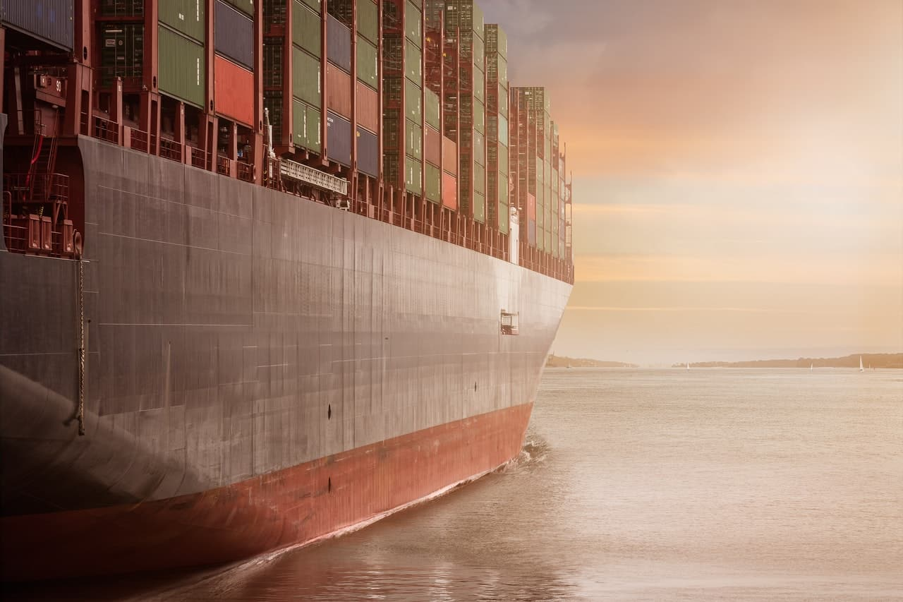 A freighter filled with cargo containers sailing toward the sunset.